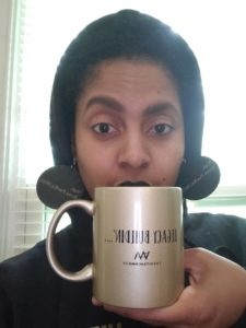 Woman wearing black Vitamin M 'Not a Trend' hoodie and holding gold mug reading 'Legacy building'